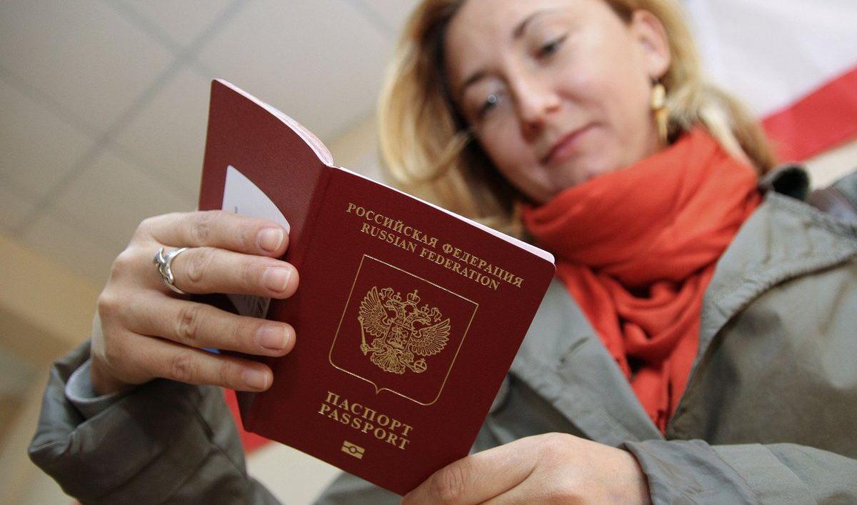 Девушка проверяет данные в выданном загран паспорте