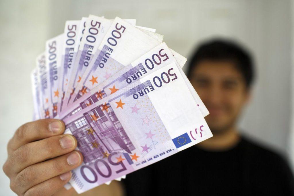 Веер из денег держит в руке