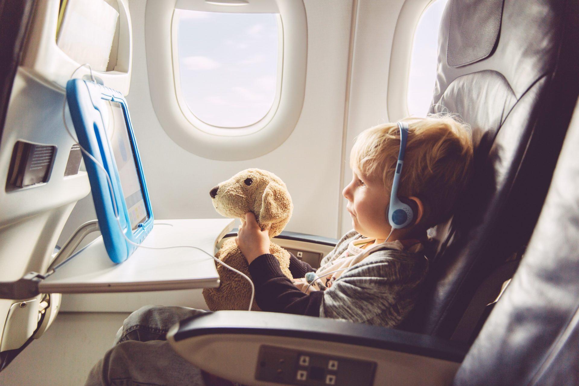 Ребенок в самолете смотрит мультфильм с планшета