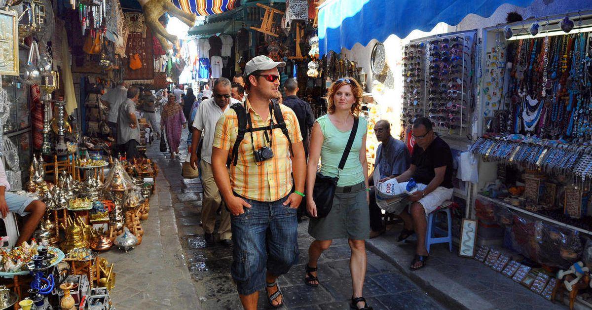 Туристы гуляют по рынку в Тунисе