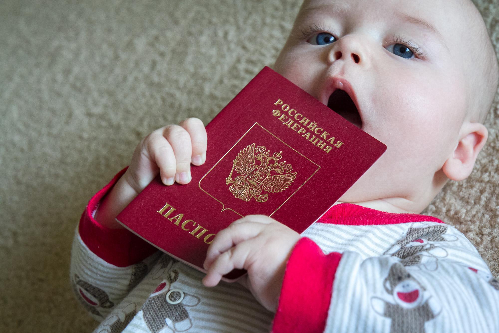 Грудничок держит свой первый загранпаспорт