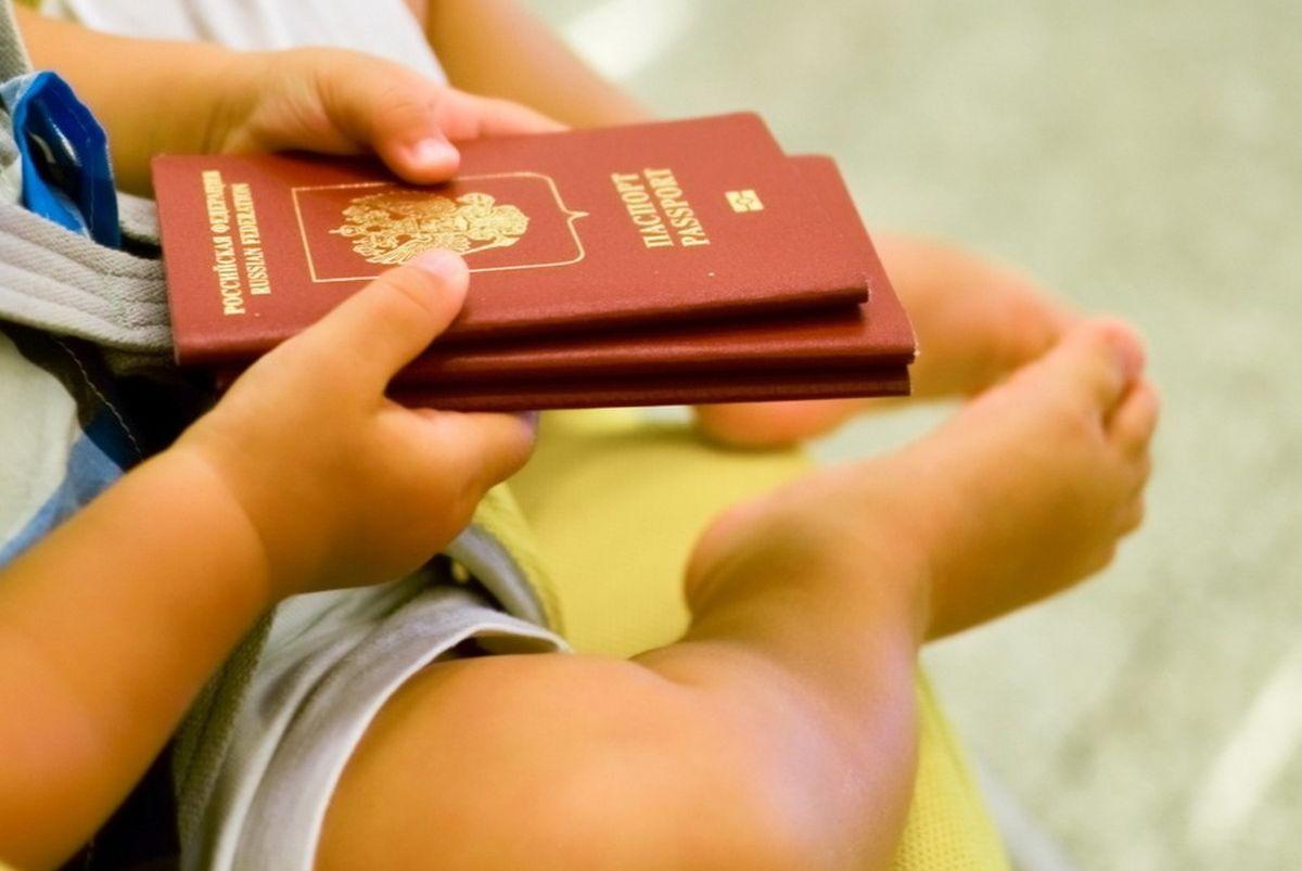 Малыш держит загранпаспорта родителей